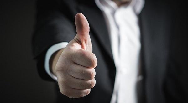 ビジネスマンが指をグッドの形にしている写真,良いビジネスの象徴