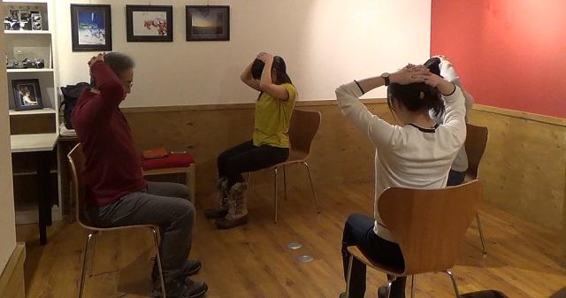 椅子ヨガ:頭の後ろで手を組んで曲げていくポーズ