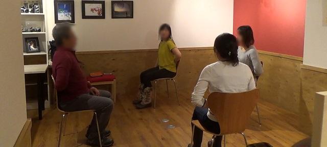 椅子ヨガで座ったまま腰を手で押すポーズの写真